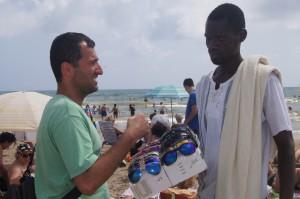 Strandverkäufer und Alireza beim Handeln